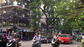 Scooters, cars, traffic, tourists, and people on the old quarter streets of the capital city, Hanoi, Vietnam. Scooters and people on the streets of Hanoi stock video footage