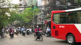 Scooters, cars, traffic, tourists, and people on the old quarter streets of the capital city, Hanoi, Vietnam. SCOOTERS AND PEOPLE ON THE STREETS OF HANOI stock video