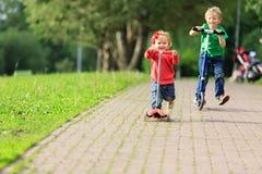 Scooters d'équitation de fille de petit garçon et d'enfant en bas âge dedans Photo libre de droits