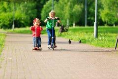 Scooters d'équitation de fille de petit garçon et d'enfant en bas âge en été Images stock