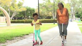 Scooters d'équitation de grand-mère et de petite-fille en parc banque de vidéos