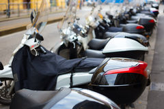 Scooters dans une rangée dans un stationnement de ville dans une profondeur de champ Image libre de droits