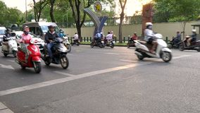 Scooters, mopeds, motorcycles, cars, traffic and people, Ho Chi Minh City, Vietnam. PEOPLE ON MOPEDS CROSSING TRAFFIC LIGHTS ON THE STREETS OF HO CHI MINH CITY stock video