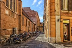 Scooters near the basilica wall in the narrow italian street stock images