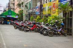 Scooters parked along the street in town. Bangkok Royalty Free Stock Photography