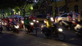 Scooters, motorcycles, cars, traffic and people on the night time streets of Ho Chi Minh City, Vietnam. Scooters and people on the streets of Ho Chi Minh City or stock footage