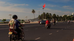 Scooters traffic along coast road in resort at dawn against flag stock video