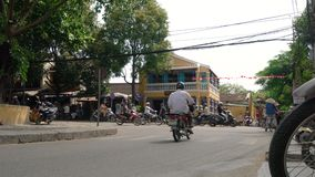 Scooters, cars, traffic, tourists, and people on the daytime streets of  Hoi An, Vietnam stock video