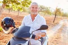 Scooteur mûr d'équitation d'homme le long de route de campagne Photographie stock