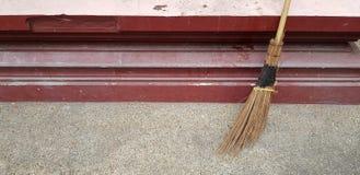 Scopa contro la parete rossa per polvere pulita e spazzare l'immondizia fotografie stock