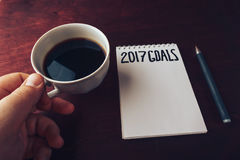 2017 scopi elencano con il taccuino, mano del ` s dell'uomo con la tazza di caffè sulla tavola di legno Immagini Stock Libere da Diritti