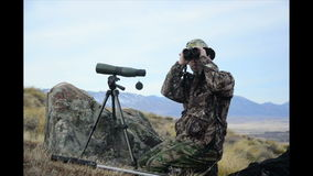 Scoping for game. A hunter in camoflage scopes for game animals such as deer, chamois and himalayan tahr in the Southern Alps of New Zealand stock footage