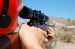 Scoping the Target. Target practice in the desert of Phoenix, Arizona.  Shooting a .22 rifle.  Aiming at paper targets Royalty Free Stock Image