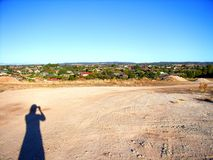 Scoping the Vacant Adelaide Land. Photograph taken of vacant land at Modbury Heights in Adelaide featuring the silhouette of a woman checking out the block ( royalty free stock photography