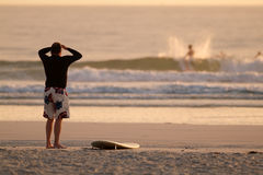 Scoping the waves. Surfer checking out the waves on the beach Royalty Free Stock Image