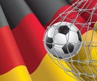 Scopo di calcio. Bandiera tedesca con un pallone da calcio. Fotografia Stock