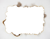 Scorched frame on paper. Burnt hole Royalty Free Stock Photo