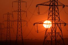Scorched pylon. Setting Sun seen through a row of electricity pylons stock photos