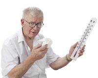 Scorching Heat!. A senior man looking miserable as he holds a wiping tissue and thermometer reading in the high 90s F. On a white background stock image