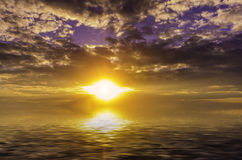 Scorching sun descending into the depths of the sea Stock Photos