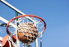 Score. A basketball going through a hoop with blue sky in background royalty free stock images