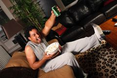 Score. A man with football, popcorn and drink excited about a score for his team Stock Images