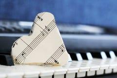 Score en gros plan de musique sur le clavier de piano, coeur de papier Photographie stock libre de droits