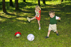 Score a goal!. Two small children playing ball on the grass in the summer stock photo