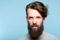 Scornful disdainful arrogant look haughty man. Man with a scornful disdainful arrogant look. portrait of a haughty young bearded guy on blue background. emotion stock photo
