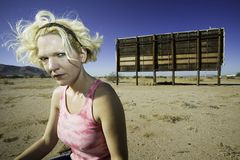 Scornful Woman. Woman with a sour expression in front of an old billboard waiting in the desert Royalty Free Stock Photography