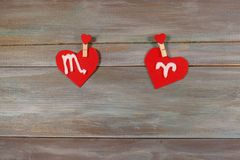 Scorpio and Aries. signs of the zodiac and heart. wooden backgro royalty free stock photos