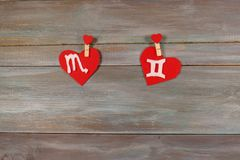 Scorpio and twins. signs of the zodiac and heart. wooden backgro. Und. card. Love. unusual handwork royalty free stock images