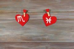 Scorpion et poissons signes du zodiaque et de coeur Backgro en bois Image stock