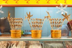 Scorpions on sticks and other weird snacks at Wangfujing snack street, Beijing. BEIJING, CHINA - DEC 25, 2013 - Scorpions on sticks and other weird snacks at royalty free stock image