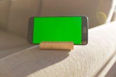 Scorrendo sullo schermo di verde dello smartphone e rilassarsi il bello giorno fotografie stock