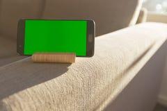 Scorrendo sullo schermo di verde dello smartphone e rilassarsi il bello giorno con spazio fotografia stock libera da diritti