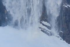 Scorrevole della neve nell'inverno nelle montagne con le rocce fotografia stock