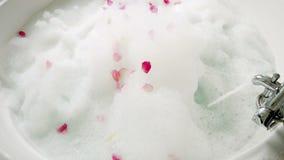 Scorrimenti dell'acqua dal rubinetto in un bagno con schiuma stock footage