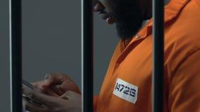 Scorrimento afroamericano del prigioniero sullo smartphone, oggetti severi in prigione stock footage