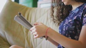 Scorrimento attraente della giovane donna sulla compressa digitale stock footage