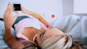 Scorrimento biondo attraente sullo smartphone che si trova su lei indietro sul letto archivi video