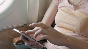 Scorrimento del passeggero dell'aeroplano tramite lo Smart Phone stock footage