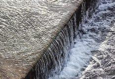 Scorrimento dell'acqua regolato di e canale di irrigazione che attraversa il mezzo di una città fotografie stock libere da diritti
