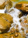 Scorrimento dell'acqua turbolento sopra la roccia immagini stock libere da diritti