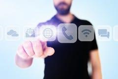 Scorrimento dell'uomo d'affari attraverso i apps di comunicazione sull'interfaccia traslucida del visualizzatore digitale fotografia stock
