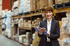 Scorrimento sorridente della donna di affari sulla compressa digitale Immagine Stock