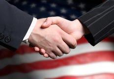 Scossa della mano e una bandiera americana Fotografia Stock Libera da Diritti