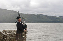 Scot playing bagpipes in front of the lake. Old Scot plays bagpipes in front of the Loch Ness lake in Scotland, UK Stock Images