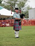 A Scot Playing Pipes. A piper playing with his band in a circle, competing against other pipe bands for honours. This piper is wearing the Ancient Lindsay tartan royalty free stock photos