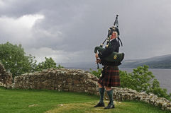 Scot plays bagpipes in front of Loch Ness. A man in traditional Scottish clothes, plays bagpipes in the yard of ruins of Urquhart castle, right beside the Loch Royalty Free Stock Photo